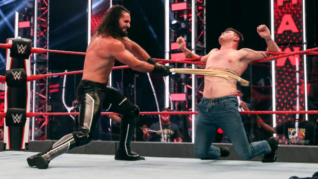WWE's Seth Rollins hits Dominik Mysterio with a kendo stick in the ring on Raw