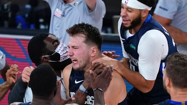 Dallas Mavericks' Luka Doncic, center, celebrates with teammates after making a game-winning 3-point basket against the Los Angeles Clippers