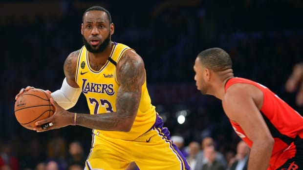 Los Angeles Lakers forward LeBron James controls the ball against Houston Rockets guard Eric Gordon during a game at Staples Center.