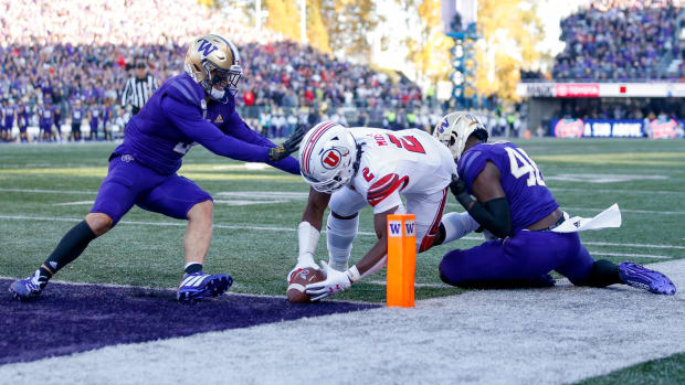 Elijah Molden and Eddie Ulofoshio of the UW can't keep Utah's Zack Moss out of the end zone.