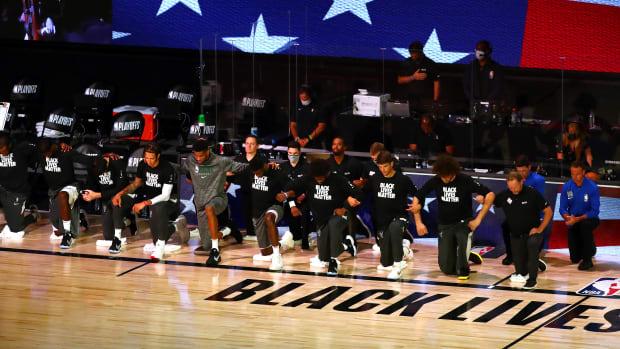 The Milwaukee Bucks kneeling on the court