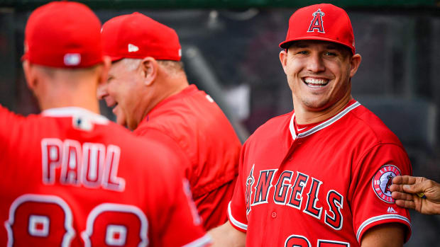 Mike Trout smiles while in the Angels dugout