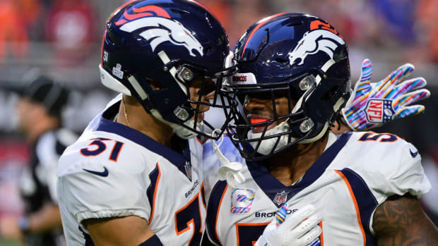 Denver Broncos linebacker Todd Davis (51) celebrates with free safety Justin Simmons (31) after returning an interception for a touchdown during the first half against the Arizona Cardinals at State Farm Stadium.