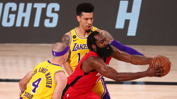 Houston Rockets guard James Harden (13) drives against Los Angeles Lakers guard Alex Caruso (4) and guard Danny Green (14) in the second half in game four of the second round of the 2020 NBA Playoffs