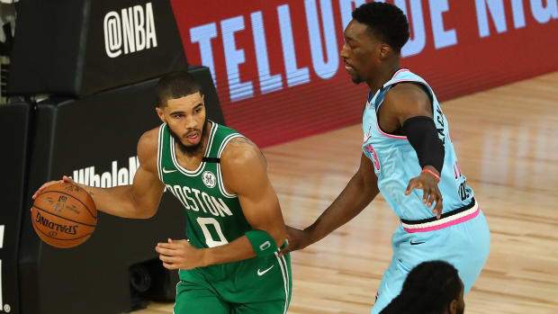 Boston Celtics forward Jayson Tatum controls the ball against Miami Heat forward Bam Adebayo in the second half of a NBA basketball game