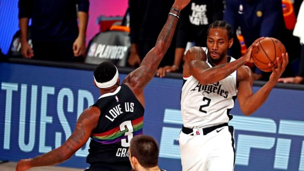 Los Angeles Clippers forward Kawhi Leonard passes the ball against Denver Nuggets forward Torrey Craig during the second round of the 2020 NBA Playoffs at ESPN Wide World of Sports Complex.