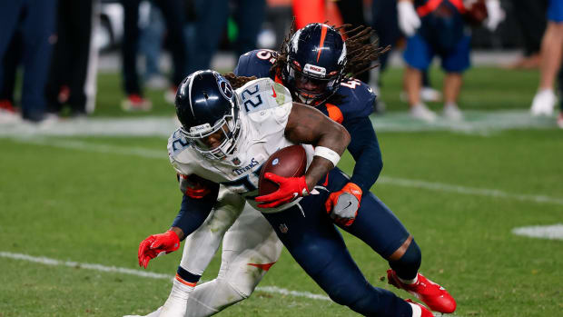 Tennessee Titans running back Derrick Henry (22) is tackled by Denver Broncos linebacker A.J. Johnson (45) in the fourth quarter at Empower Field at Mile High.