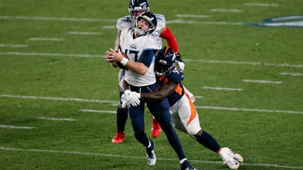 Tennessee Titans quarterback Ryan Tannehill (17) is sacked by Denver Broncos linebacker Jeremiah Attaochu (97) in the second quarter at Empower Field at Mile High.