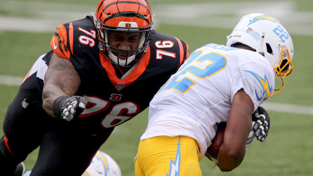 Cincinnati Bengals defensive tackle Mike Daniels (76) tackles Los Angeles Chargers running back Justin Jackson (22) in the first quarter during a Week 1 NFL football game against the Los Angeles Chargers, Sunday, Sept. 13, 2020, at Paul Brown Stadium in Cincinnati. Los Angeles Chargers At Cincinnati Bengals Sept 13