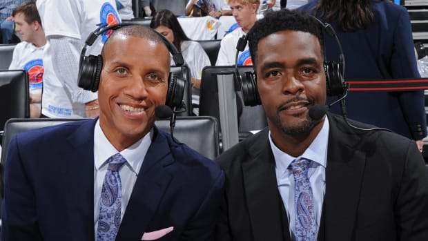 Reggie Miller and Chris Webber pose courtside behind the broadcast booth.