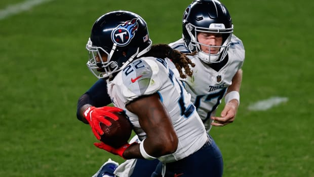 Tennessee Titans quarterback Ryan Tannehill (17) hands the ball off to running back Derrick Henry (22) in the second quarter against the Denver Broncos at Empower Field at Mile High.
