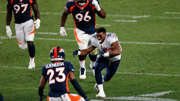 Tennessee Titans running back Dalyn Dawkins (28) runs the ball against Denver Broncos cornerback Michael Ojemudia (23) and defensive end Shelby Harris (96) after losing his helmet in the third quarter at Empower Field at Mile High.