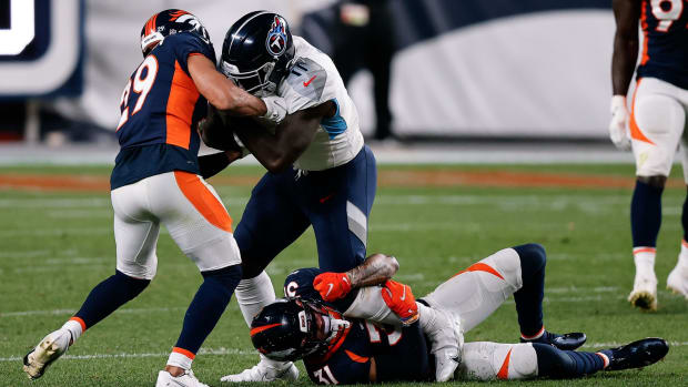 Tennessee Titans wide receiver A.J. Brown (11) is tackled by Denver Broncos free safety Justin Simmons (31) and cornerback Bryce Callahan (29) in the third quarter at Empower Field at Mile High.