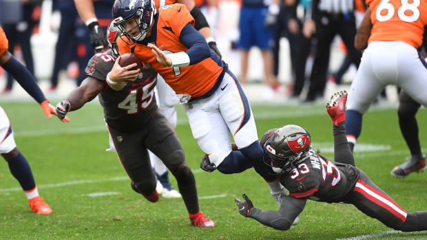 Tampa Bay Buccaneers inside linebacker Devin White (45) and free safety Jordan Whitehead (33) sack Denver Broncos quarterback Jeff Driskel (9) in the second quarter at Empower Field at Mile High.