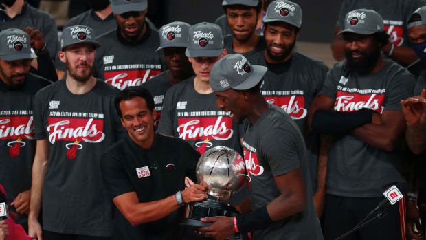 Miami Heat head coach Erik Spoelstra hands the Eastern Conference Championship trophy to forward Bam Adebayo (13) after defeating the Boston Celtics in game six of the Eastern Conference Finals of the...