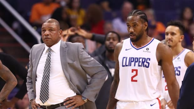 Former Los Angeles Clippers coach Doc Rivers and current forward Kawhi Leonard leave the huddle against the Phoenix Suns at Talking Stick Resort Arena.