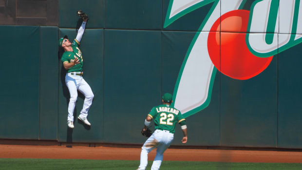 Mark Canha skies up against the wall in left-center to make a catch some compare to Joe Rudi's in the 1972 World Series.