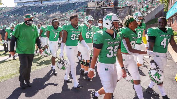 Marshall football players walk to the tunnel