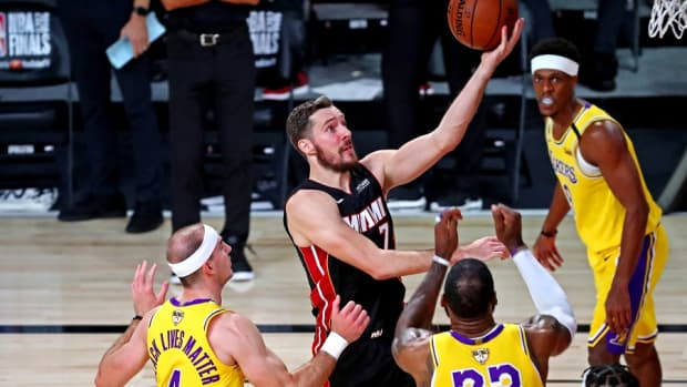 Miami Heat guard Goran Dragic drives against Los Angeles Lakers guard Alex Caruso and forward LeBron James during the 2020 NBA Finals at AdventHealth Arena.