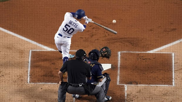 Sep 30, 2020; Los Angeles, California, USA; Los Angeles Dodgers right fielder Mookie Betts (50) follows through on a double in the first inning as Milwaukee Brewers catcher Omar Narvaez (10) and umpire Mark Ripperger (90) watch during Game 1 of the National League Wild Card Playoffs at Dodger Stadium. Mandatory Credit: Kirby Lee-USA TODAY Sports
