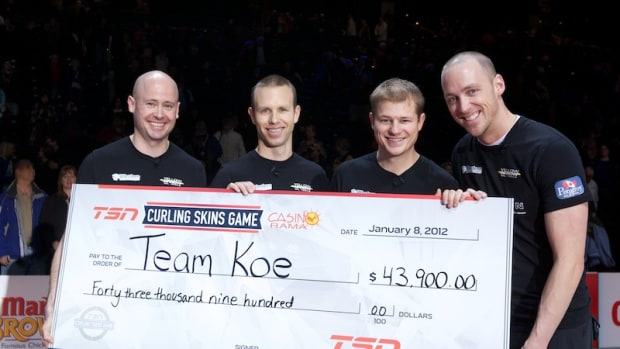 Team Koe with the cheque they are trying to take as carry-on for their flight home.