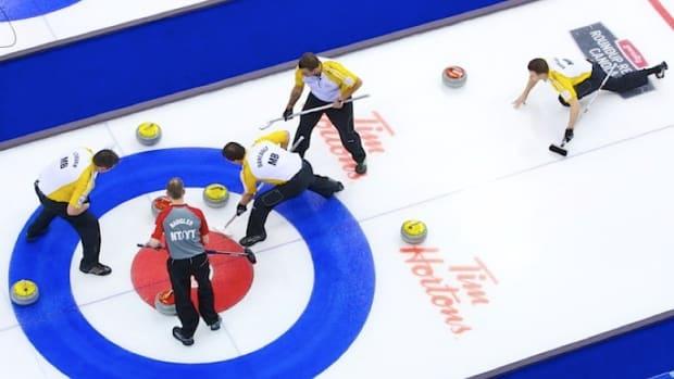 Manitoba skip Rob Fowler (right) slides into play