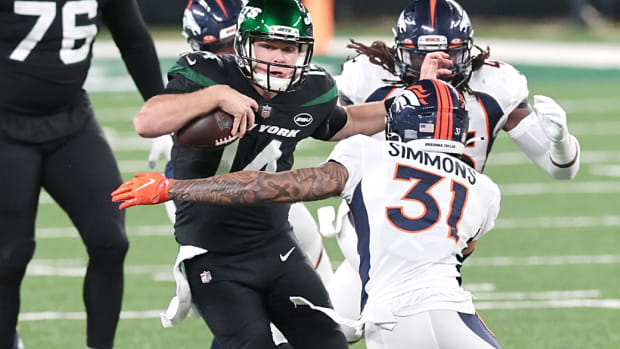 New York Jets quarterback Sam Darnold (14) breaks a tackle by Denver Broncos free safety Justin Simmons (31) for a touchdown at MetLife Stadium.
