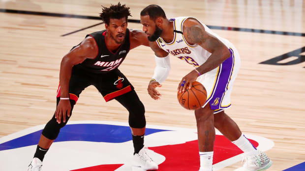 Lakers forward LeBron James dribbles while defended by Heat forward Jimmy Butler during the 2020 NBA Finals.