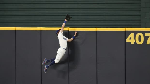 Oct 7, 2020; Arlington, Texas, USA; Los Angeles Dodgers center fielder Cody Bellinger (35) leaps at the wall and robs a home run from San Diego Padres shortstop Fernando Tatis Jr. (not pictured) during the seventh inning in game two of the 2020 NLDS at Globe Life Field. Mandatory Credit: Tim Heitman-USA TODAY Sports
