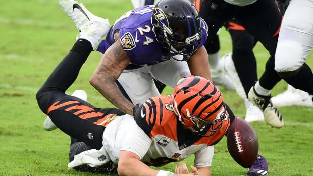 Oct 11, 2020; Baltimore, Maryland, USA; Cincinnati Bengals quarterback Joe Burrow (9) fumbles while being sacked by Baltimore Ravens cornerback Marcus Peters (24) in the third quarter at M&T Bank Stadium. Mandatory Credit: Evan Habeeb-USA TODAY Sports