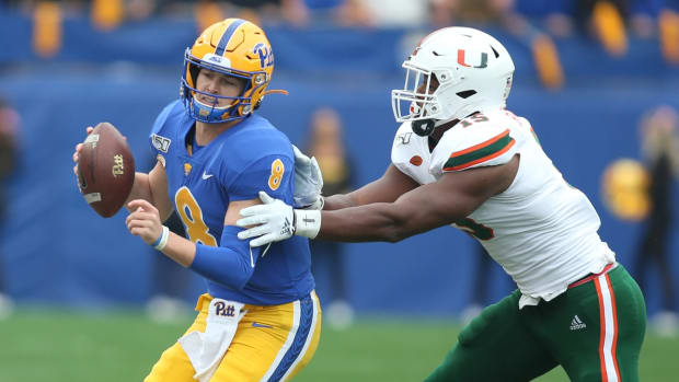 Pittsburgh Panthers quarterback Kenny Pickett (8) is chased by Miami Hurricanes defensive lineman Gregory Rousseau (15) during the first quarter at Heinz Field.