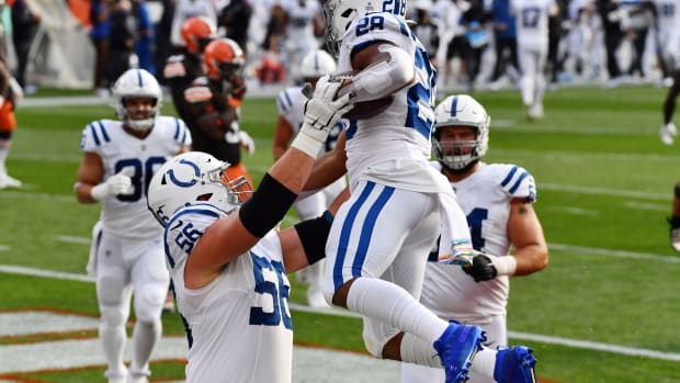 Indianapolis Colts offensive guard Quenton Nelson (56) lifts rookie running back Jonathan Taylor after a TD rush on Sunday at Cleveland.
