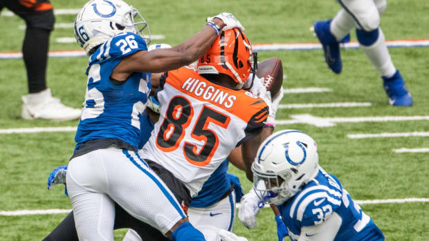 Oct 18, 2020; Indianapolis, Indiana, USA; Cincinnati Bengals wide receiver Tee Higgins (85) catches the ball with Indianapolis Colts cornerback Rock Ya-Sin (26) and free safety Julian Blackmon (32) defending in the second half at Lucas Oil Stadium. Mandatory Credit: Trevor Ruszkowski-USA TODAY Sports