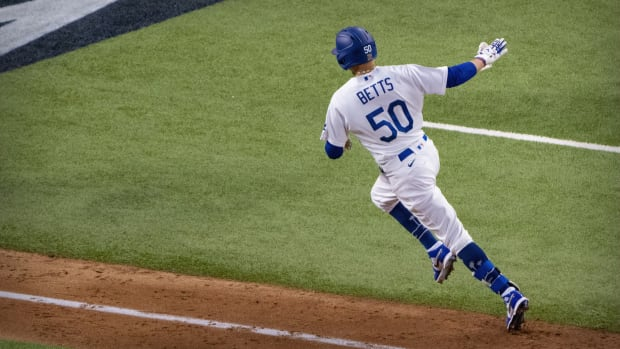 Oct 20, 2020; Arlington, Texas, USA; Los Angeles Dodgers right fielder Mookie Betts (50) hits a home run against the Tampa Bay Rays during the sixth inning in game one of the 2020 World Series at Globe Life Field. Mandatory Credit: Jerome Miron-USA TODAY Sports