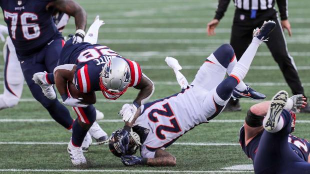 Denver Broncos saftey Kareem Jackson (22) tackles New England Patriots running back James White (28) during the second half at Gillette Stadium.