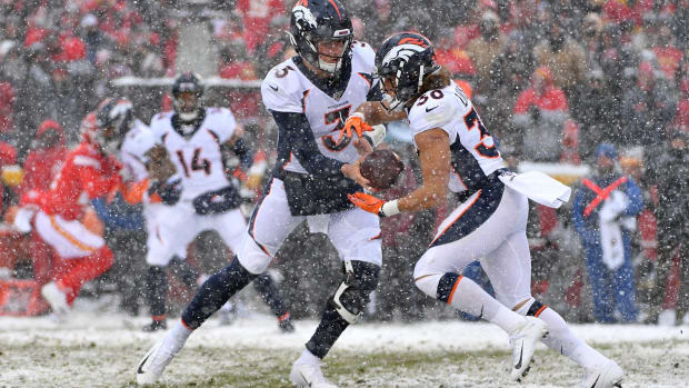 Denver Broncos quarterback Drew Lock (3) hands off to running back Phillip Lindsay (30) during the game against the Kansas City Chiefs at Arrowhead Stadium.