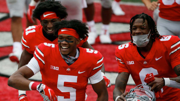 Ohio State Buckeyes wide receiver Garrett Wilson (5) smiles as he heads to the locker room with safety Josh Proctor (41) and wide receiver Jameson Williams (6) following the Buckeyes 52-17 vic...