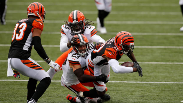 Cincinnati Bengals wide receiver Mike Thomas (80) is brought down after making the first down by Cleveland Browns free safety Andrew Sendejo (23) in the fourth quarter of the NFL Week 7 game between the Cincinnati Bengals and the Cleveland Browns at Paul Brown Stadium in downtown Cincinnati on Sunday, Oct. 25, 2020. The Bengals and Browns exchanged late touchdowns, finishing in a 37-34 win for the Browns. Cleveland Browns At Cincinnati Bengals