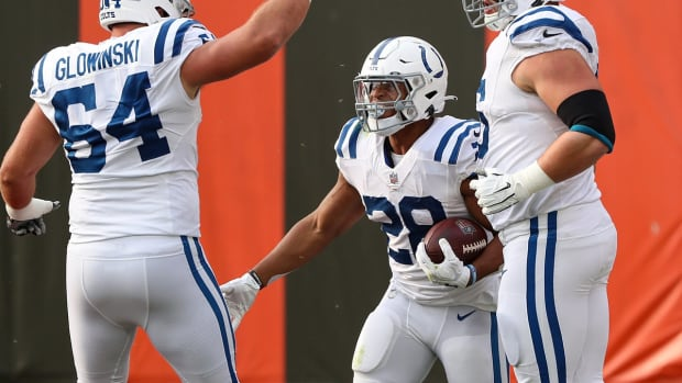 Indianapolis Colts rookie running back Jonathan Taylor (28) celebrates a touchdown run at Cleveland with guards Mark Glowinski (64) and Quenton Nelson.