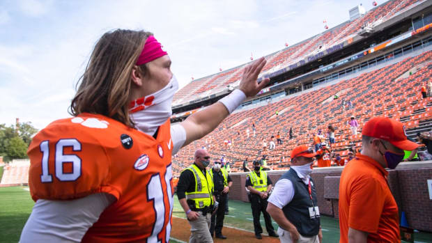 Clemson QB Trevor Lawrence waves to fans while wearing a mask