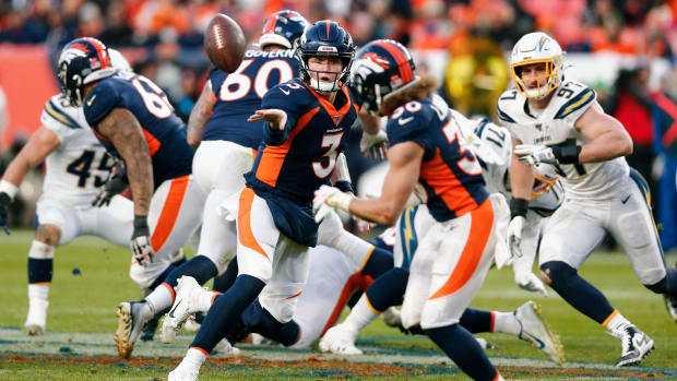Denver Broncos quarterback Drew Lock (3) pitches the ball to running back Phillip Lindsay (30) in the third quarter against the Los Angeles Chargers at Empower Field at Mile High.