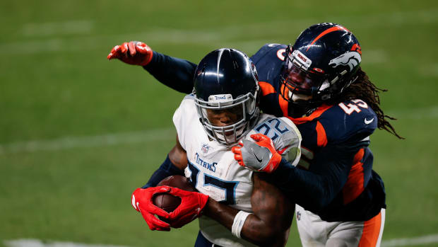 Tennessee Titans running back Derrick Henry (22) is tied up by Denver Broncos linebacker A.J. Johnson (45) in the fourth quarter at Empower Field at Mile High.