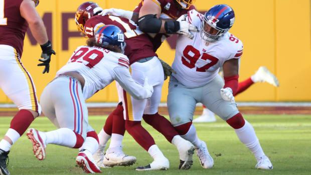 Nov 8, 2020; Landover, Maryland, USA; Washington Football Team quarterback Alex Smith (11) is sacked by New York Giants defensive end Leonard Williams (99) in the third quarter at FedEx Field.