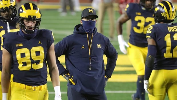 Michigan head coach Jim Harbaugh watches as his team warms up before playing Wisconsin at Michigan Stadium