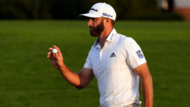 Dustin Johnson waves after putting out on the 18th green during the third round of The Masters golf tournament at Augusta National GC.