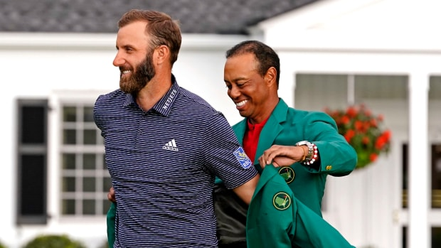 2019 Masters champion Tiger Woods presents Dustin Johnson with the green jacket after winning The Masters golf tournament