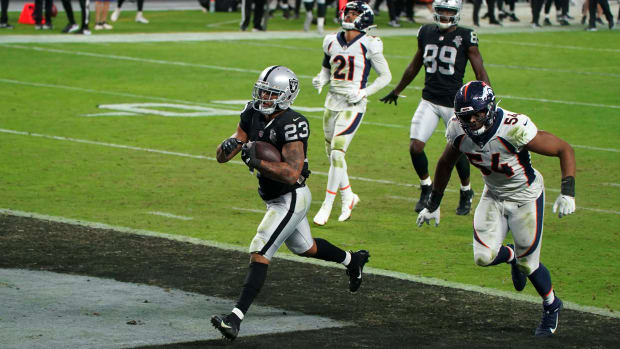 Las Vegas Raiders running back Devontae Booker (23) is pursued by Denver Broncos linebacker Josh Watson (54) on a 23-yard touchdown run in the fourth quarter at Allegiant Stadium. The Raiders defeated the Broncos 37-12.