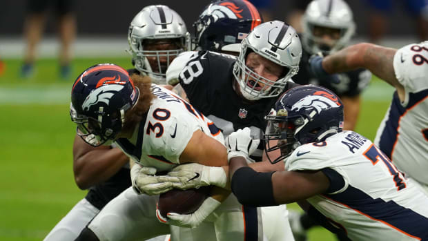 Las Vegas Raiders defensive end Maxx Crosby (98) tackles Denver Broncos running back Phillip Lindsay (30) in the first half at Allegiant Stadium.