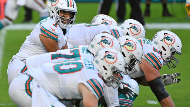 Miami Dolphins quarterback Tua Tagovailoa (1) looks over the offensive line during the first half against the Los Angeles Chargers at Hard Rock Stadium.