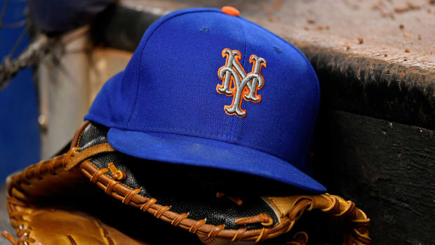 Mets hat sitting on top of glove